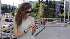 Young brunette with curly hair in sun glasses uses a smart phone Stock Footage