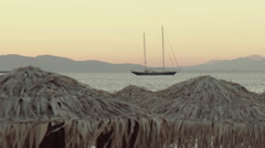 Evening at Greek island beach,umbrellas and sailing yacht in the sea ,pan Stock Footage
