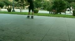 Back of teenage boy roller-skating on walkway in park Stock Footage