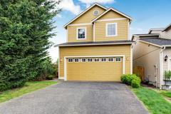 Curb appeal. Yellow two level house exterior with garage. Northwest, USA Stock Photos
