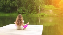 Little girl is engaged in yoga on wooden bridge Stock Footage