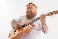 Happy male guitarist performing music Stock Photos