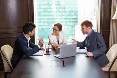Three Business People Discussing Issues Stock Photos