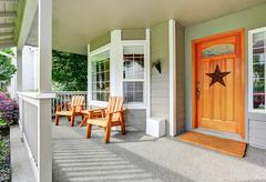 Spacious concrete floor porch with wooden chairs and nice entry door. Northwe Stock Photos