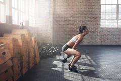 Tough young woman exercising with kettle bell at gym Stock Photos