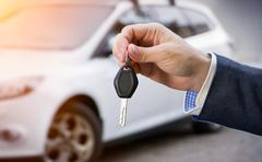Male holding car keys with car on background Stock Photos