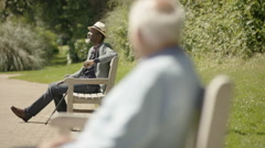 4K Senior man relaxing in the park on a sunny day with man in background Stock Footage