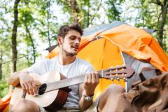 Smiling young man tourist sitting and playing guitar in forest Stock Photos