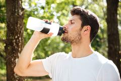 Handsome young man athlete drinking water in forest Stock Photos
