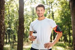 Cheerful young sportsman standing and drinking water in forest - stock photo