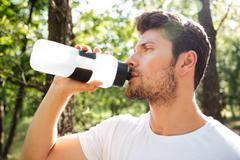 Attractive young sportsman standing and drinking water outdoors - stock photo