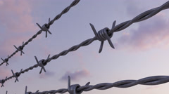 Lines of barbed wire against evening cloudy sky, loopable dolly clip. 4K - UHD Stock Footage