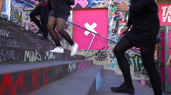 Many human feet kicking up and down the stairs with graffiti. Stock Footage