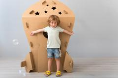 Little boy standing near carton rocket Stock Photos