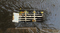 Rain water falling into sewerage Stock Footage