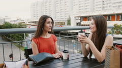 Beautiful women drinking coffee communicate in a cafe with a view of the traffic Stock Footage