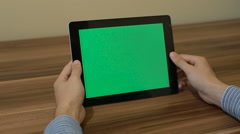 Man Using Tablet zoom out hand with Green Screen on the Background of Table. Stock Footage
