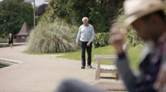 4K Senior gents walking & relaxing in the park on a sunny day Stock Footage