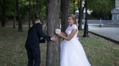 Bride and groom hiding behind a tree and kissing Stock Footage