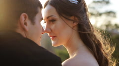 Close up portrait of charming bride and elegant groom on landscapes of sunset Stock Footage