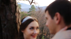 Close-up of of romantic newlywed couple lean back on tree in sunny day - stock footage