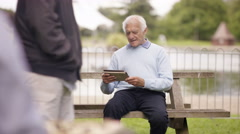 4K Senior gent relaxing in the park & using tablet computer Stock Footage