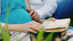Pregnant woman and her husband reading a book in a scene not seen people Stock Footage