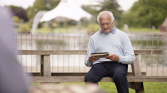 4K Senior man relaxing in the park & making video call with tablet computer Stock Footage