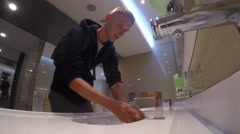 Young Man Washing Hands in Sink after Pee in Public Toilet. 4K. Stock Footage