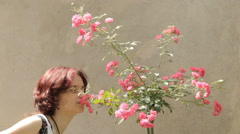 Young woman with rosebush Stock Footage