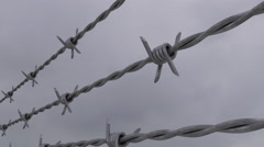Barbed wire against grey cloudy sky, loopable dolly clip. 4K Stock Footage