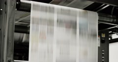 Newspapers move along a conveyor belt at a newspaper factory. Stock Footage