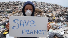 Woman with Save Planet Board Against Garbage Dump Stock Footage