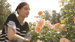 Girl sniffs roses with lens flare Stock Footage