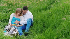 A pregnant woman with her husband considered toys for their unborn baby Stock Footage