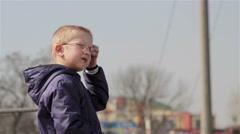 Boy standing on the side of the highway waiting for school bus. Stock Footage