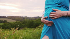 Pregnant woman stroking her belly, walks in nature - stock footage