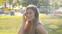 Young beautiful woman enjoying music outdoors on headphones Stock Footage