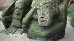 Two Stone Statues in the Moss on the Beach, Lapped by the Waves. Slow Motion Stock Footage