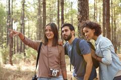 Three happy friends pointing at something in the dappled afternoon sunshine w Stock Photos