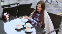 Woman pours tea from a teapot into a cup in outdoors cafe Stock Footage