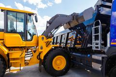 Image of yellow bulldozer load into a truck Stock Photos