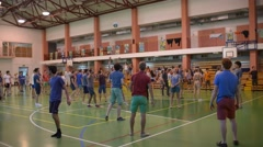 Young Catholics play a friendly game of volleyball in the gym of the school Stock Footage