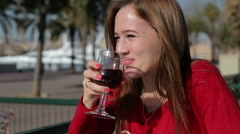 Beautiful young girl with glass of red wine alone in a street cafe Stock Footage