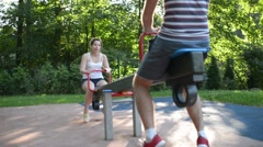 Young people boy and girl riding on a swing - romantic date Stock Footage