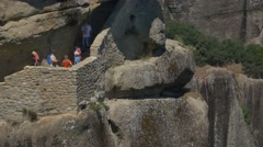Tourists taking pictures while visiting the Holy Trinity Monastery in Meteora Stock Footage