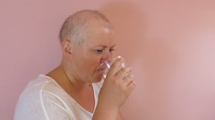 Woman with cancer is taking prescribed medicines. Side view shot Stock Footage