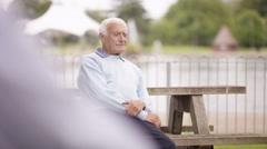 4K Portrait grumpy senior man sitting alone in the park Stock Footage