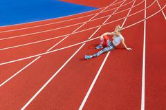 Athletic female runner rests on running track at sports arena Stock Photos