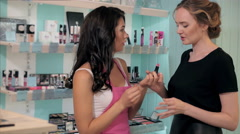 Cheerful young girl and woman choosing makeup products in beauty department with Stock Footage